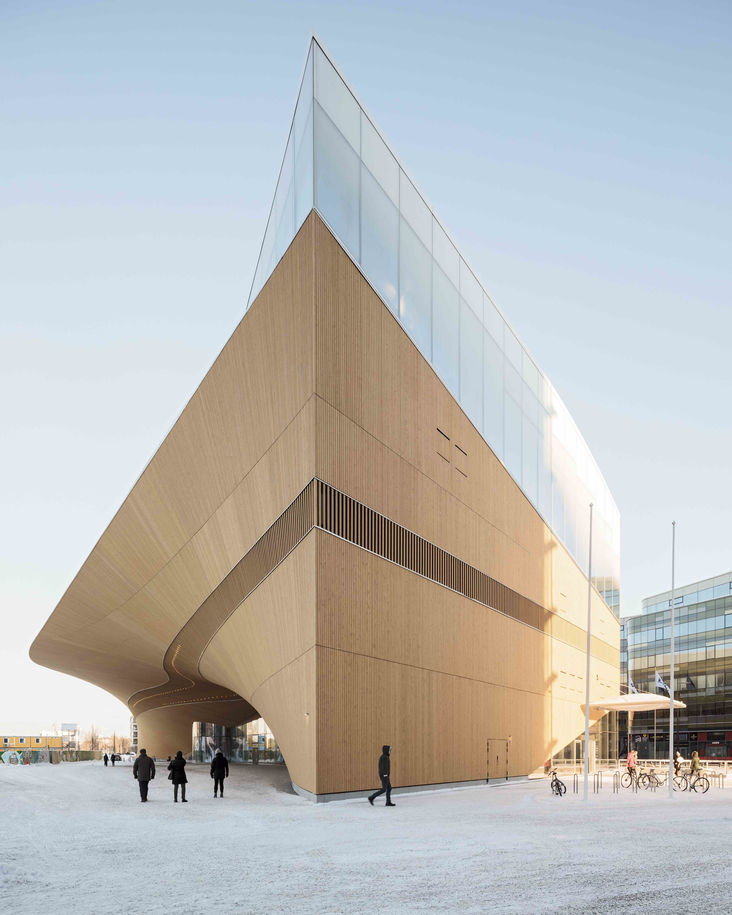 The library is accessed under a dramatic arch at street level. Photo by Tuomas Uusheimo