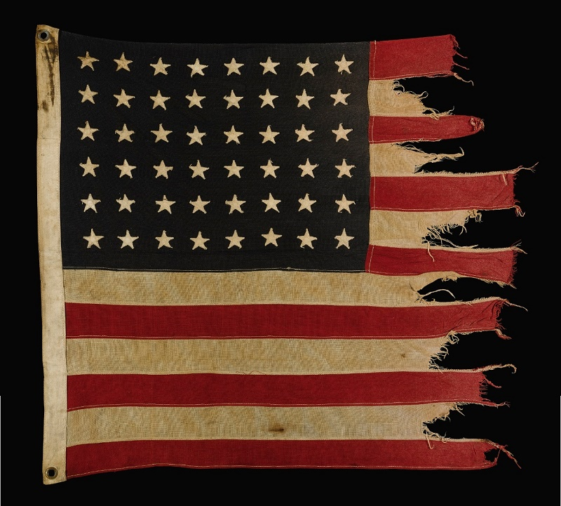 The battle-scarred US flag rescued from the wreck of the USS Corry during the D-Day landings by Lt. Paul Garay (Image: Sotheby's)