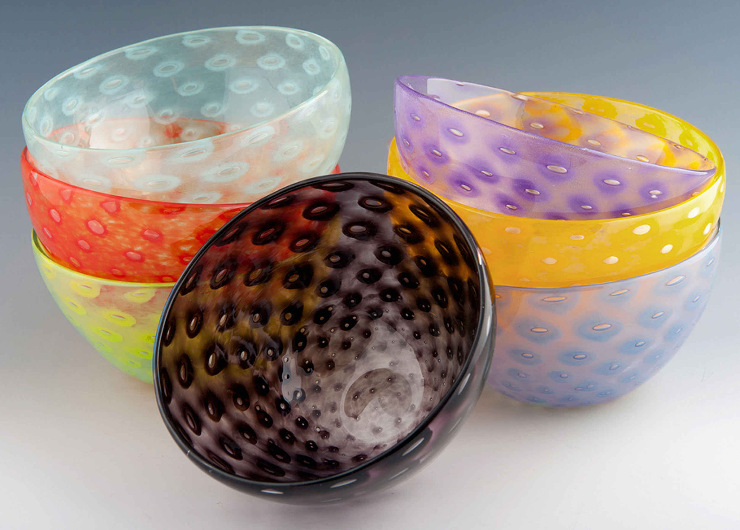 Bubble Bowl, seen here in Celadon, Vermillion, Lime (top to bottom, left stack). Black (middle), Violet, Yellow, Periwinkle (top to bottom, right stack).