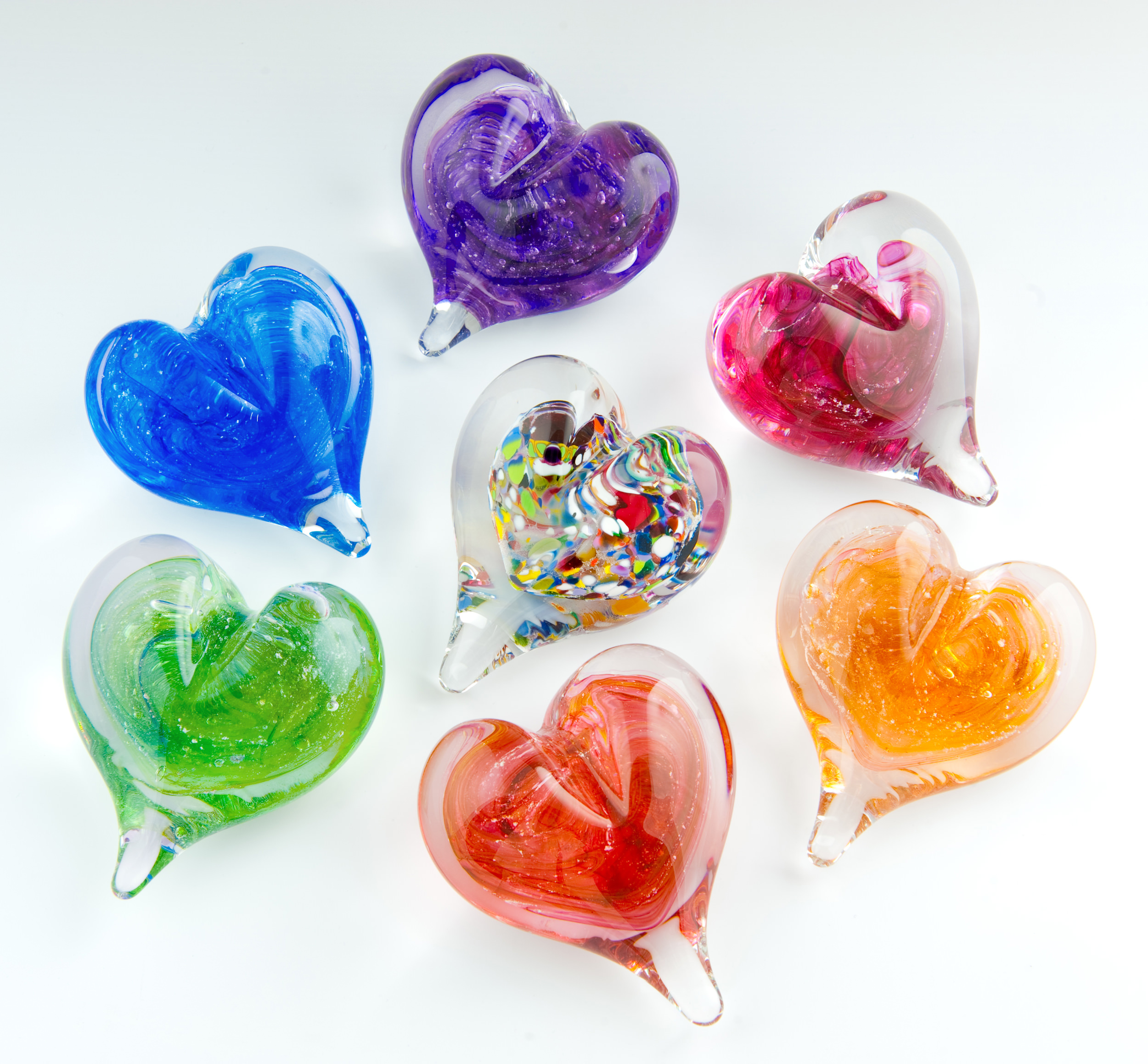 Our Heart Paperweights are seen here in Violet, Red, Blue, Multicolored, Green, Gold, and Peach.