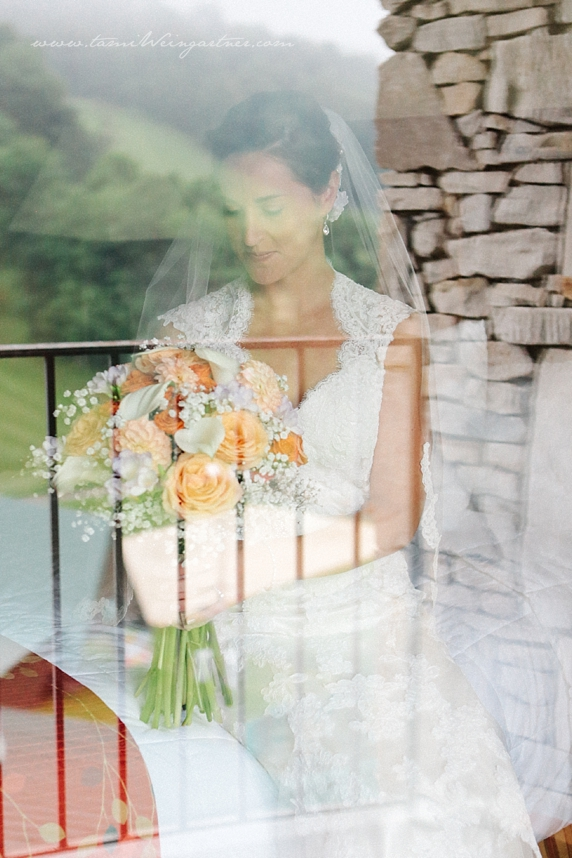 The mountain at Seven Springs Resort reflected through glass on a bride.