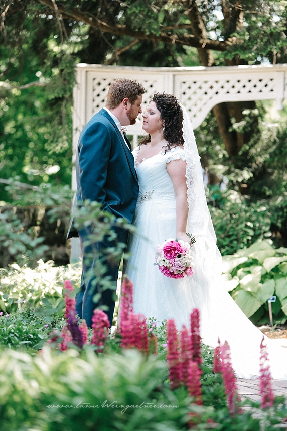 Gorgeous Bride and Groom pose in the flower garden at Fellowes Riverside Garden with purple flowers