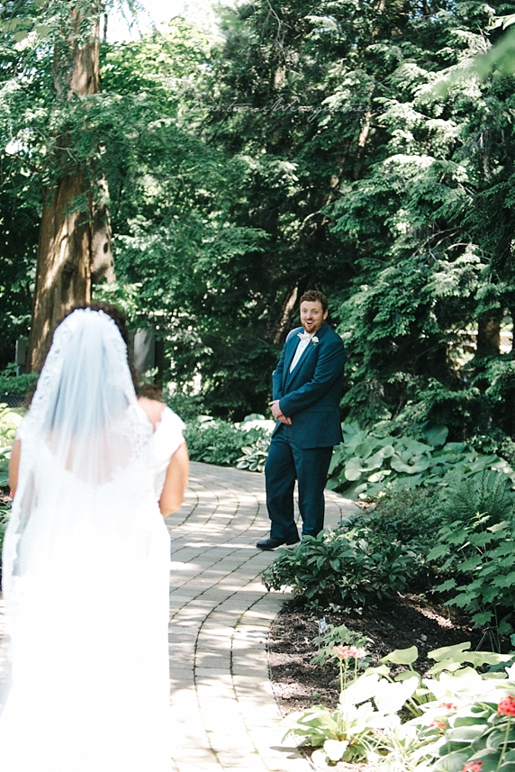 Groom getting first look at bride in sunken japanese garden in Fellows Riverside Garden in Youngstown OH