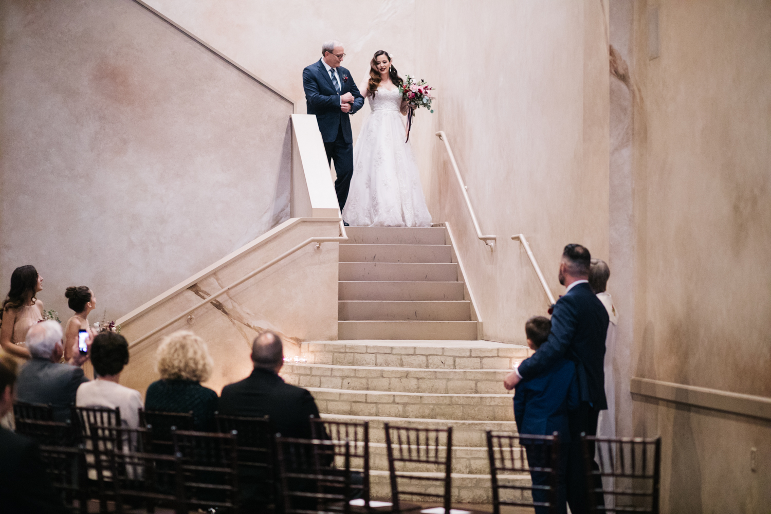 Bride coming down long staircase with her father.
