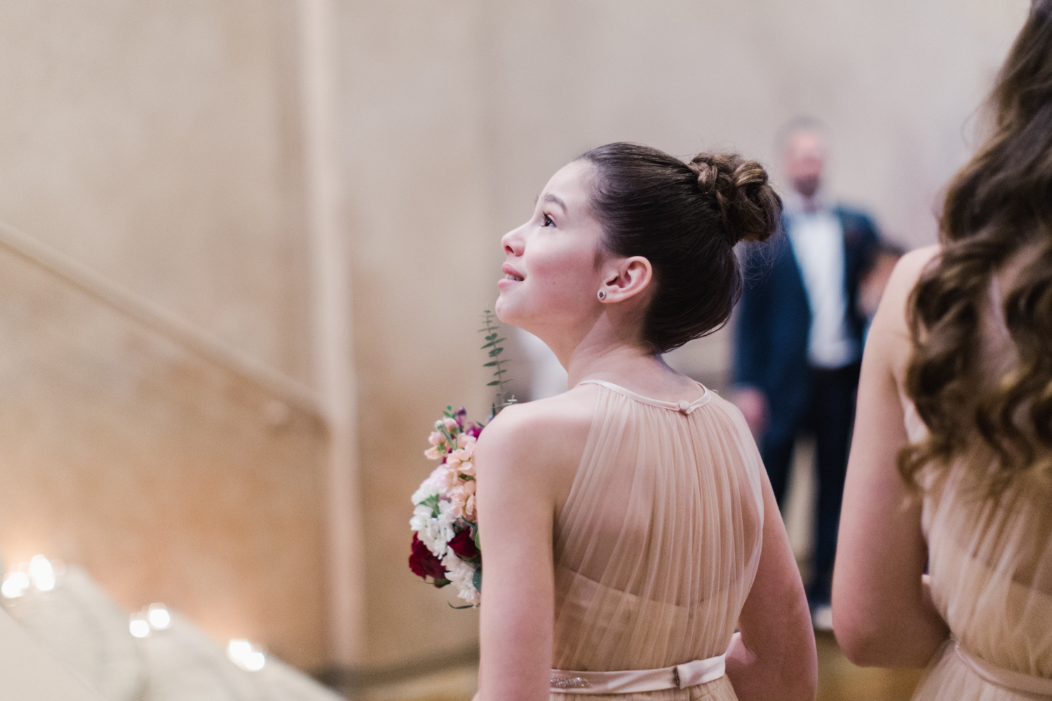 Bridesmaids watching her mother walk down the aisle with tears and emotion in her eyes.