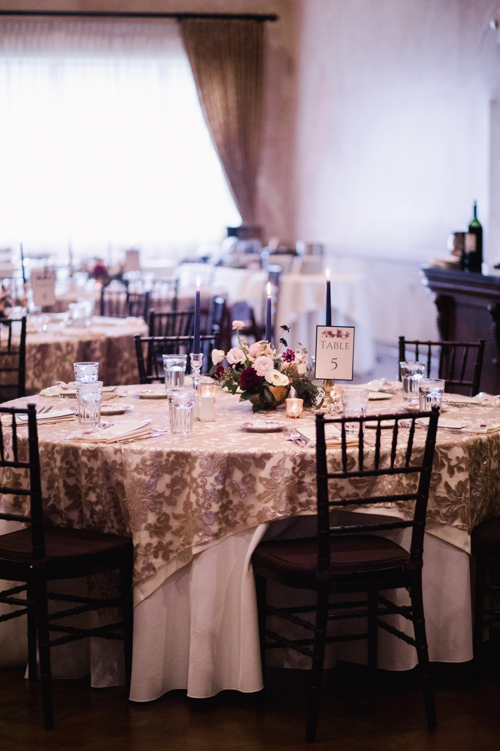 Navy colored tapers, mixed candlesticks, upgraded lines and beautiful chairs make this wedding reception romantic and soft.