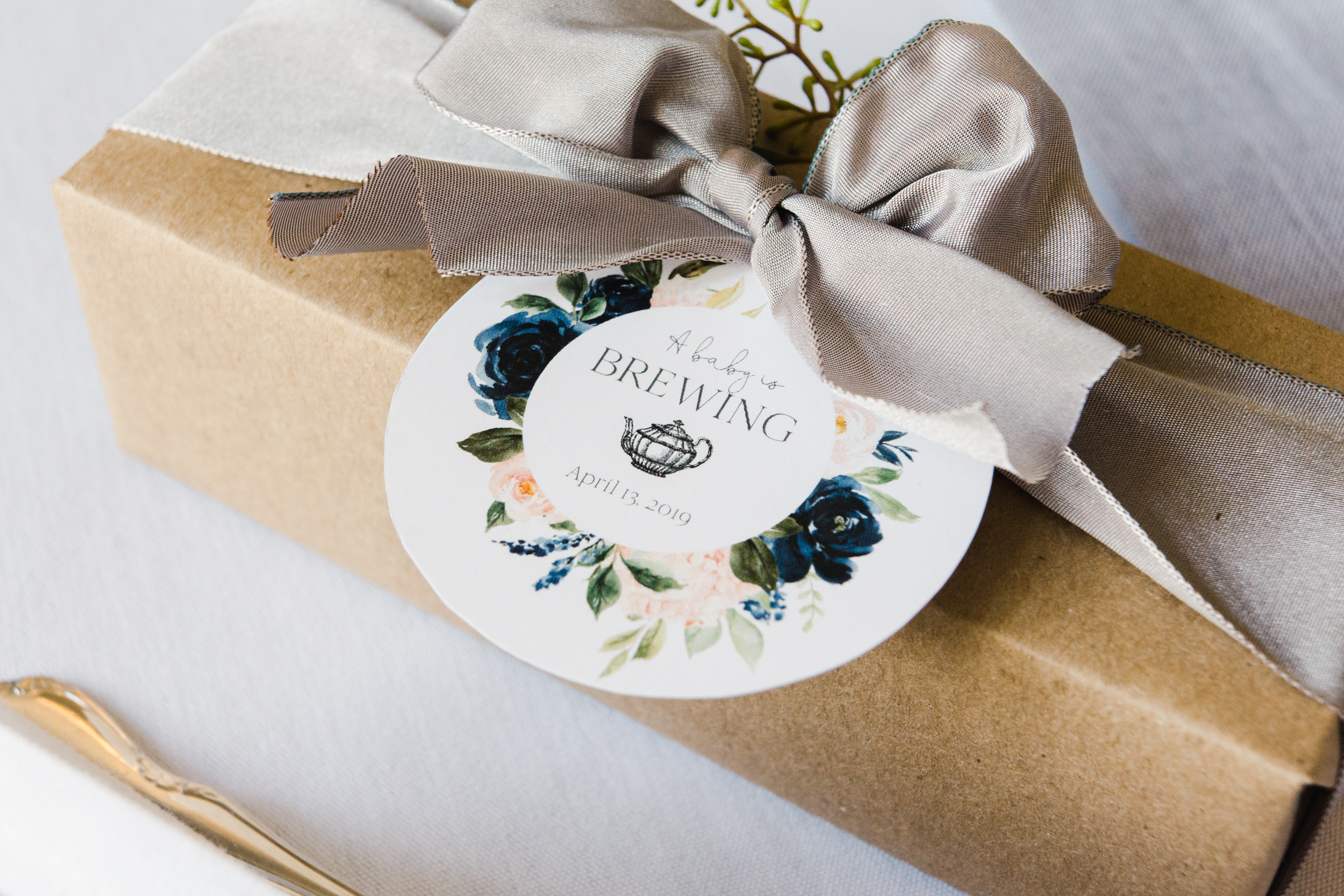 A favor box containing silk tea sachets and an assortment of almond and coffee macaroons was beautifully wrapped then hand tied with silver ribbon and included a sweet 'a baby is brewing' card in the same watercolor design as the rest of the stationary.