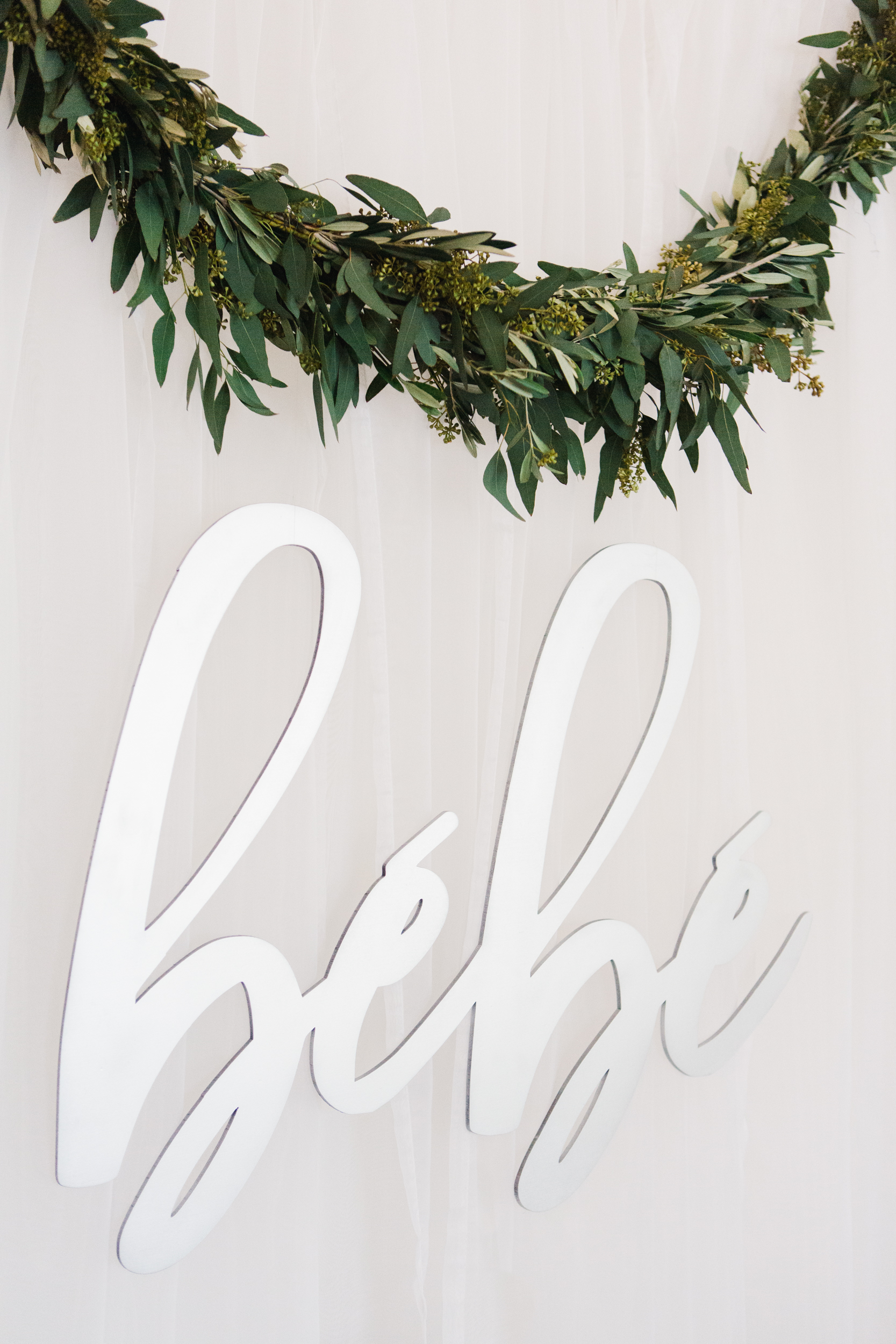 cutout silver bebe sign with a second eucalyptus swag over the brunch buffet