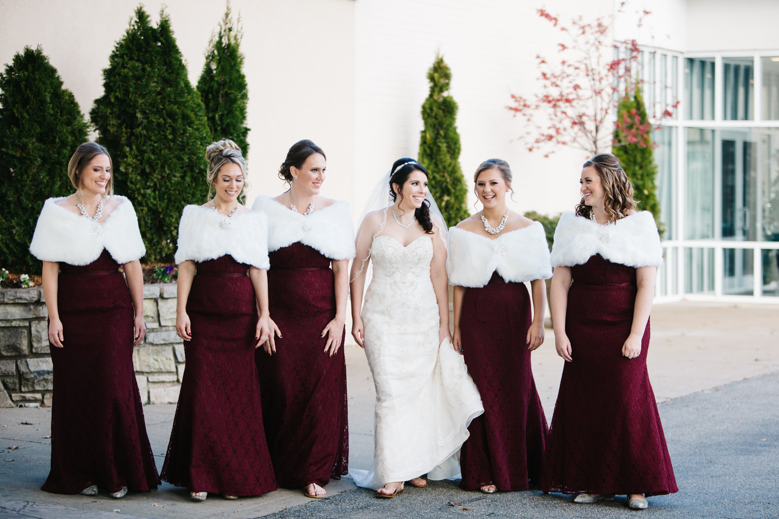 December wedding palette. Textured burgundy bridesmaid dresses with fur caplet.
