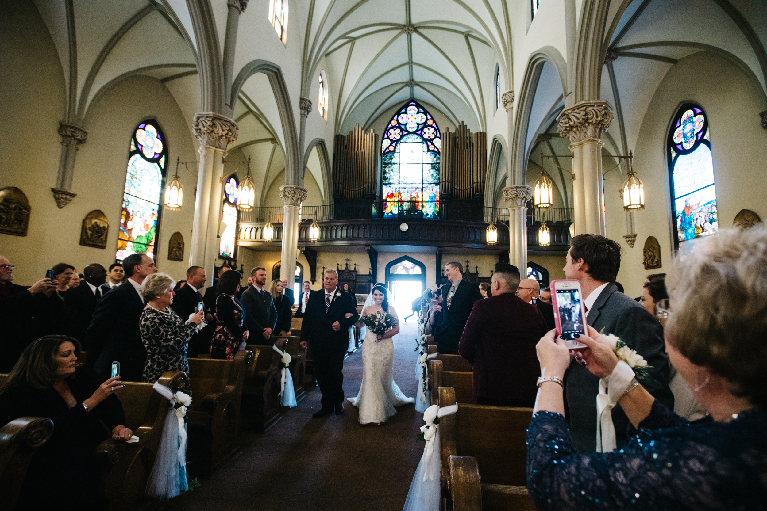 A happy beaming bride walking down the aisle at St. Mary on The Mount in Pittsburgh, PA on her wedding day.