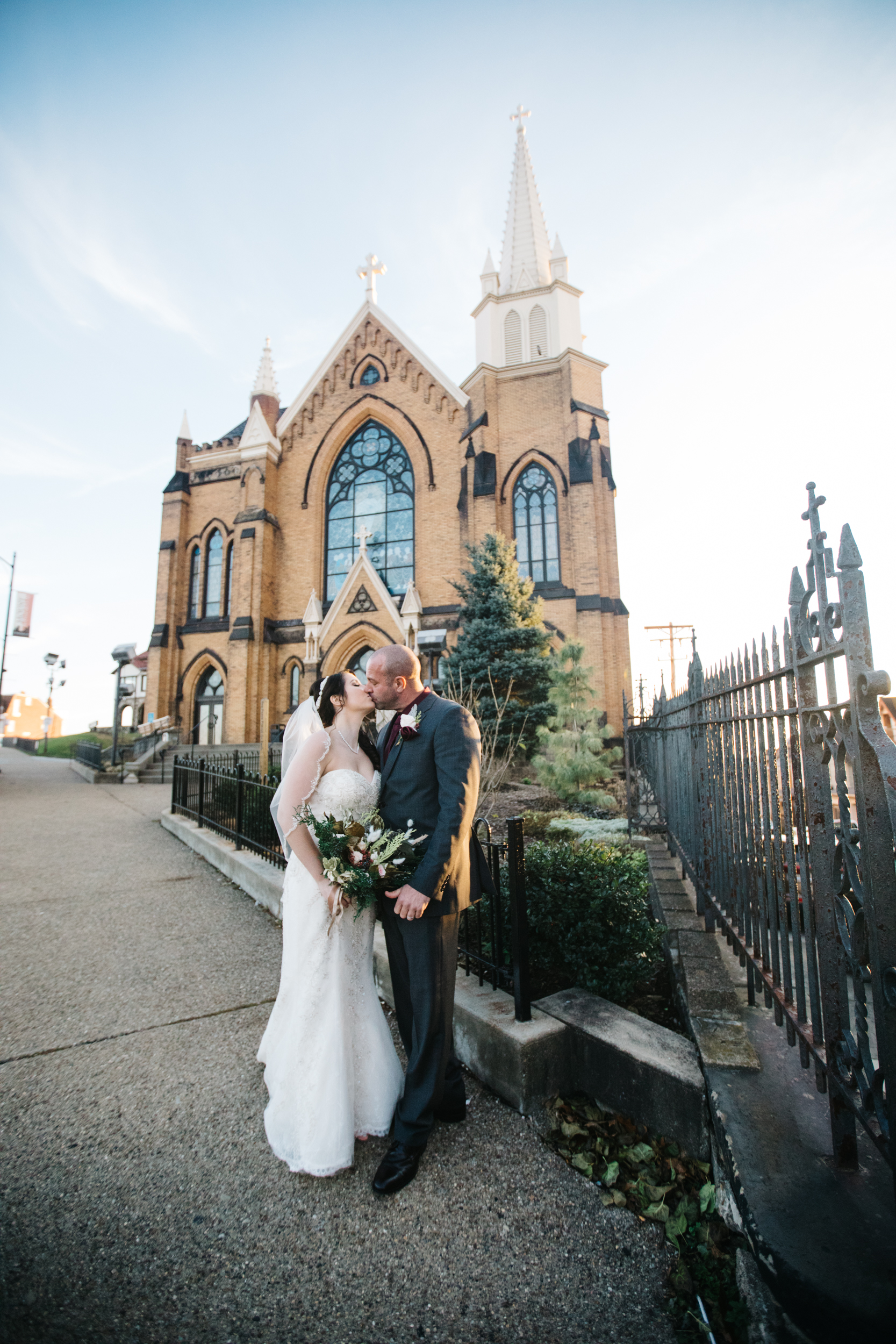 Wedding couple kissing in front of St. Mary of The Mount in Pittsburgh PA