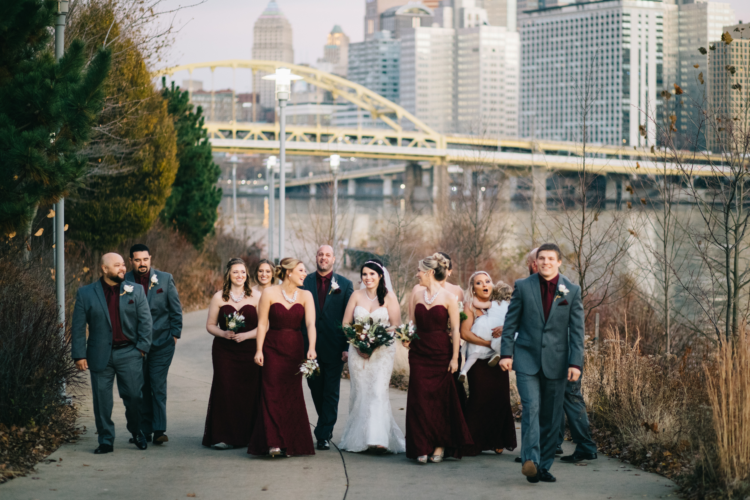 Full bridal party walking and smiling as they walk along the river beside Heinz Field with the yellow bridges and city in the background.