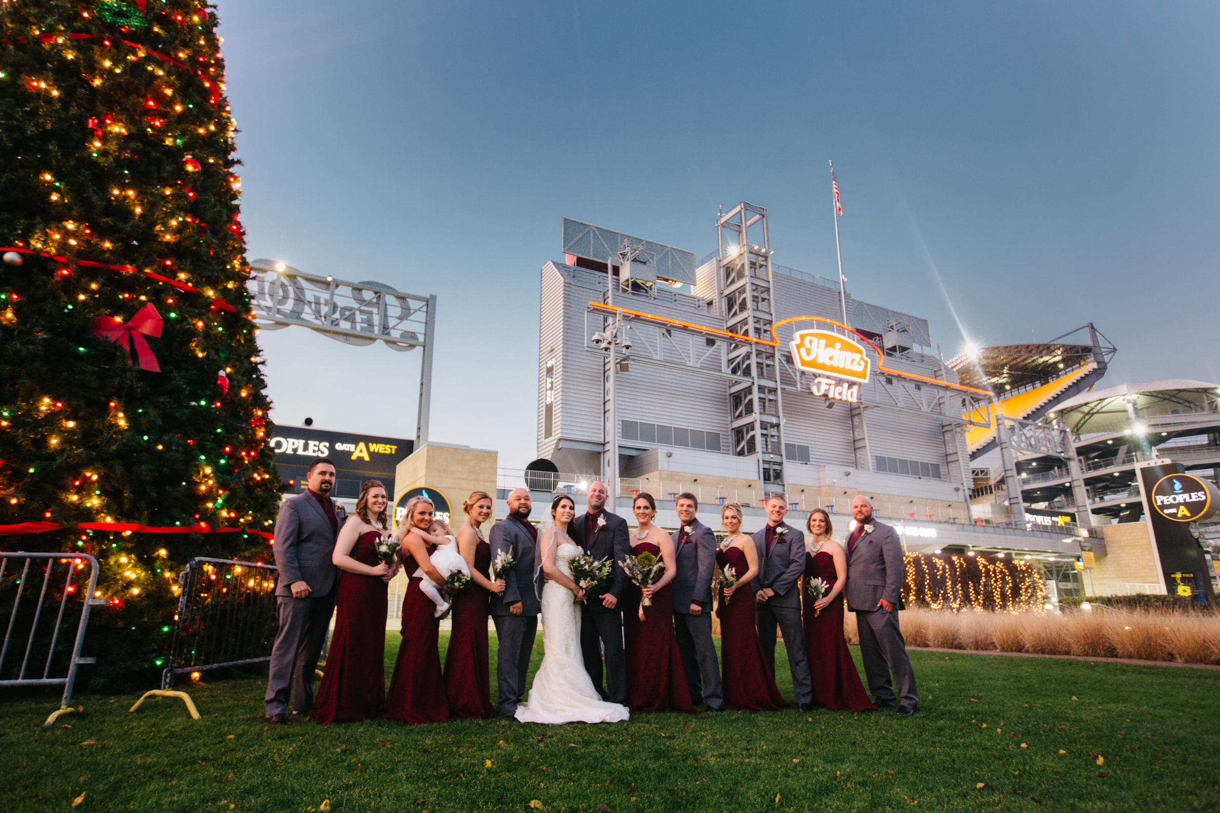 Formal bridal party posed shot at night int he winter in front of Heinz Field with a light Christmas tree.