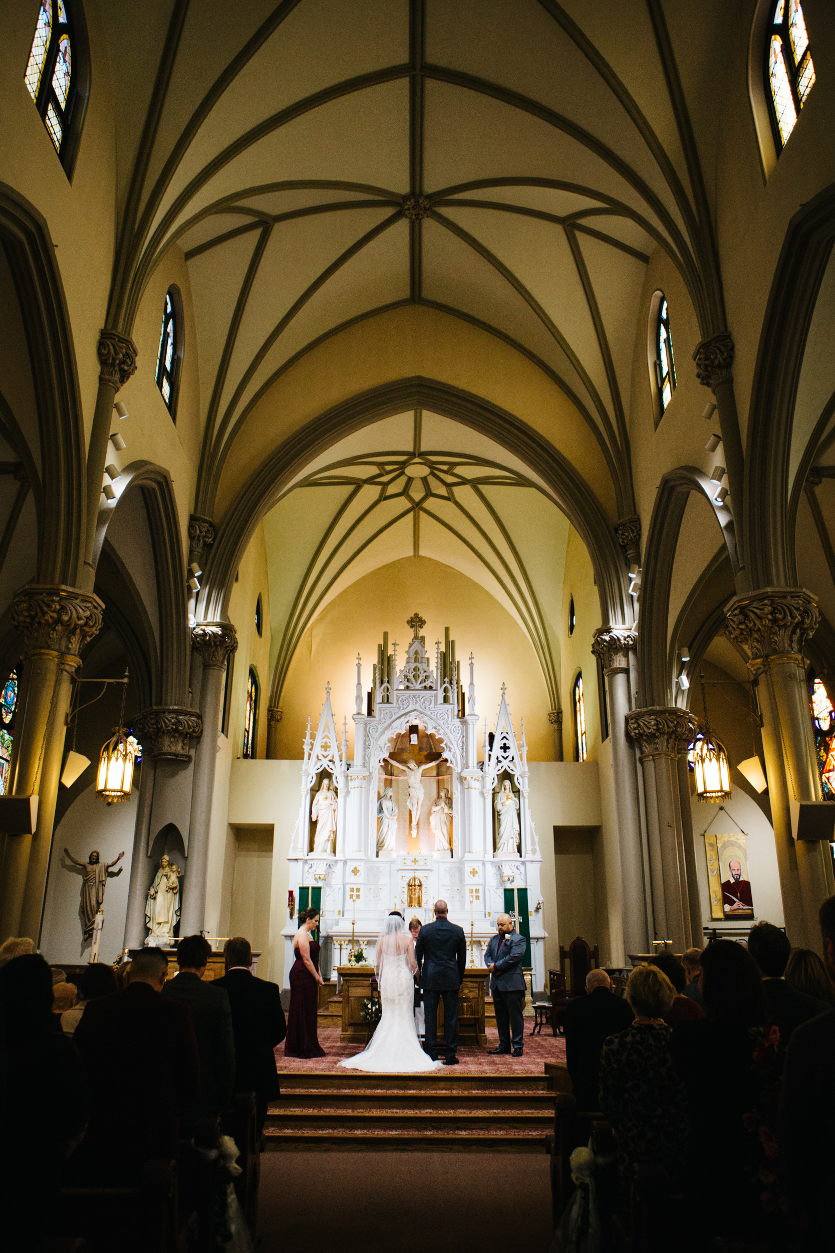 Wide angle view of the alter with a bride and groom standing in front during a wedding at St. Mary of The Mount on Grandview Ave in Pittsburgh PA.