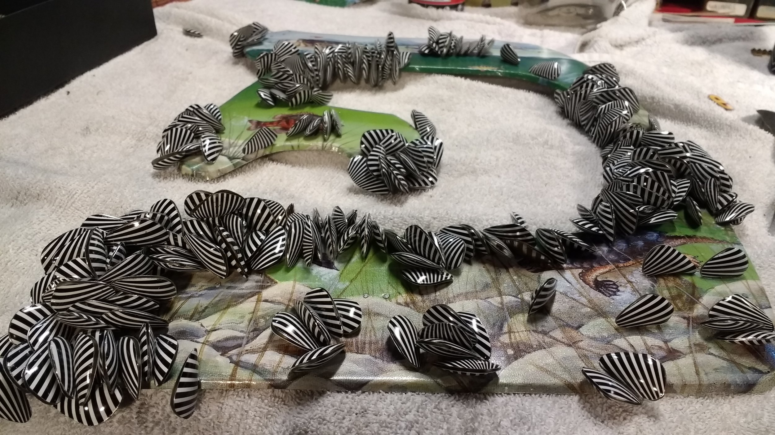 Close-up view of attaching recycle tin cans zebra mussels to a hebrew letter.
