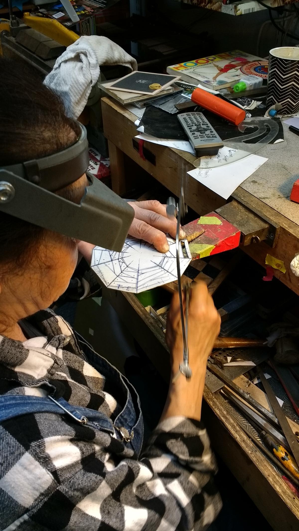 """Harriete Estel Berman working on the bracelet Alternative Facts """"web of lies"""""""