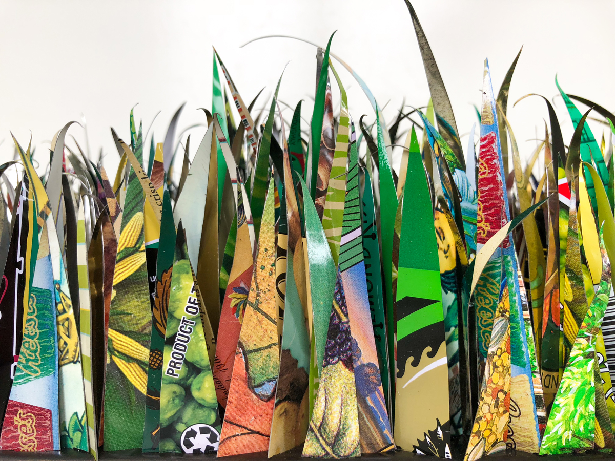 A Yard of Grass cut from recycled tin cans as a commentary about the impact of the grass lawn on the environment.