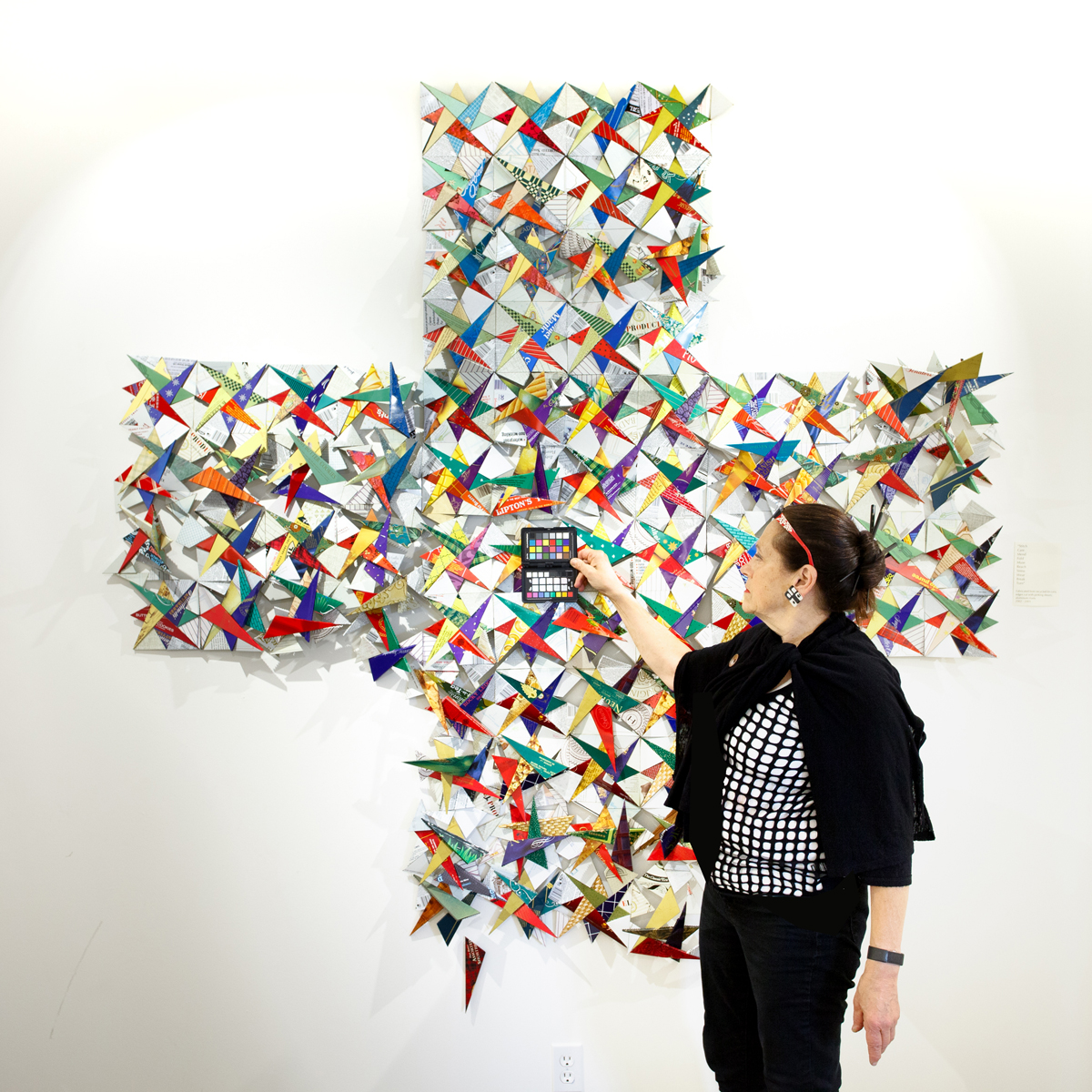 Harriete Estel Berman standing in front of quilt during photo session with Philip Cohen