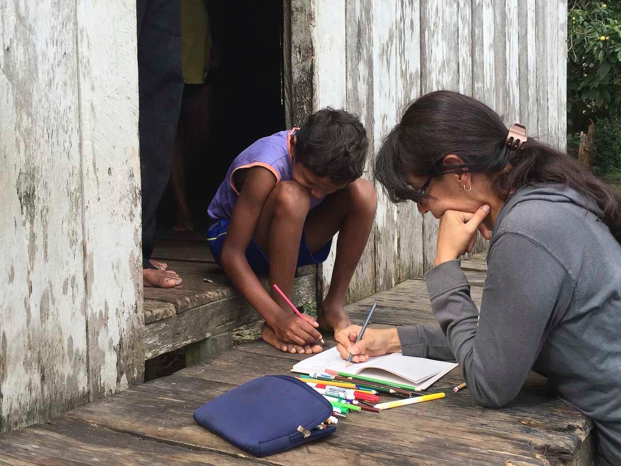 Alejandra takes notes with a family in Comunidade Deus e Pai.