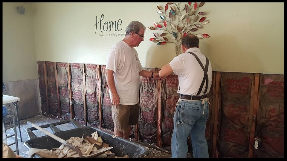 HisHands2Go staff tearing out flood-damaged drywall and insulation.