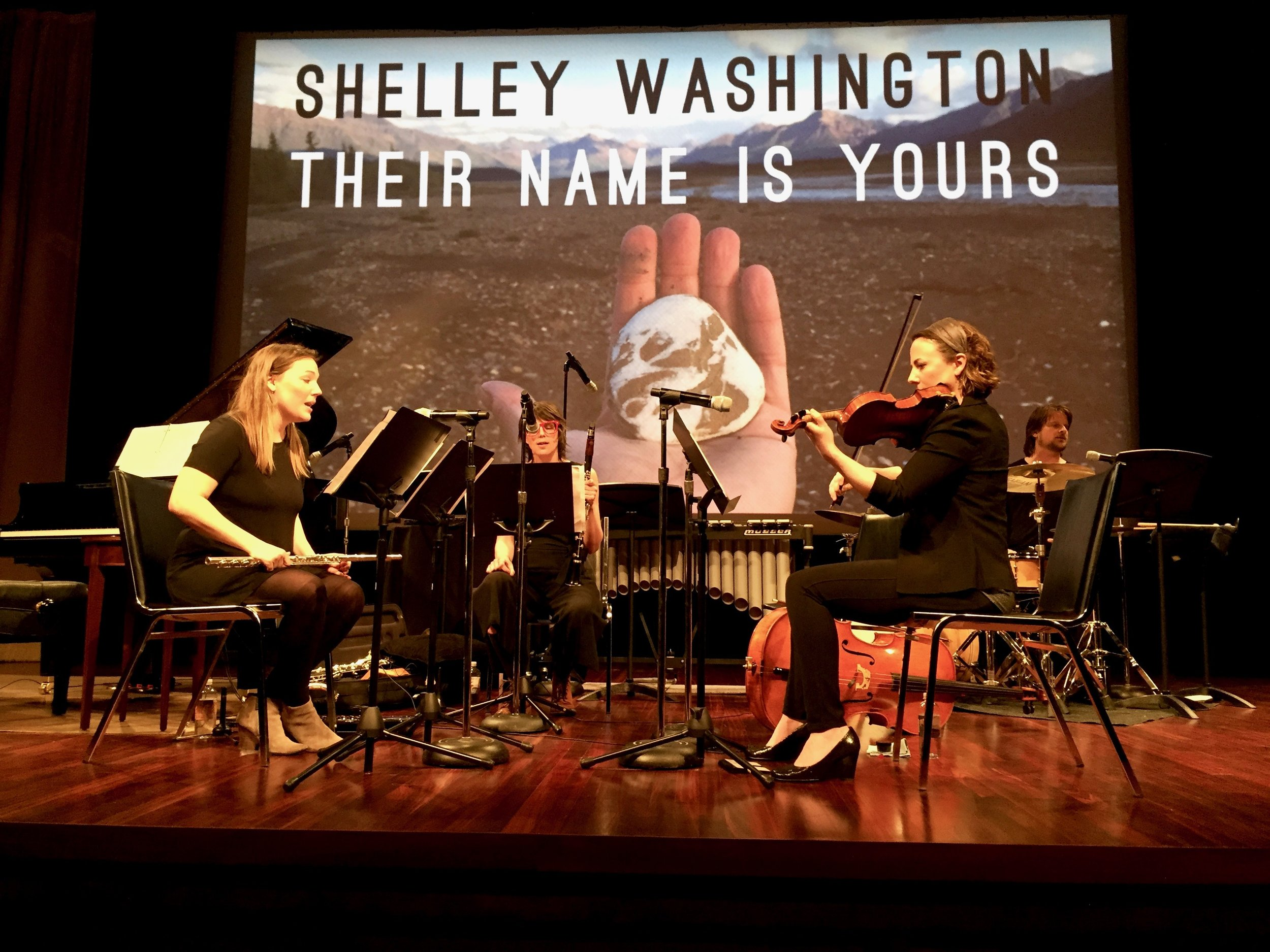 """Musicians and leaders of  Wild Shore New Music ,  Katie Cox  playing flute (left),  Andie Tanning Springer  on fiddle (right), with  Christa Van Alstine  on clarinet (center) and  Michael McCurdy  on drum set (far right) performing """"Their Name Is Yours"""" at the  U.S. National Archives  on March 30th, 2017."""