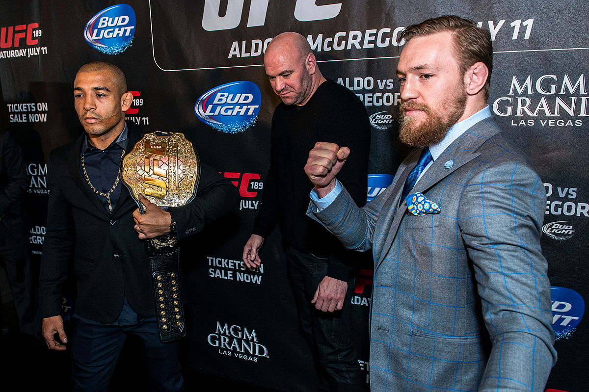 Jose Aldo and Conor McGregor pose for the cameras while Dana White mediates.