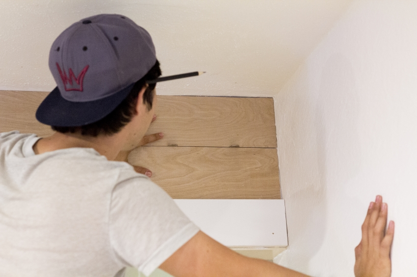 """Start at the top of your wall with your first 6"""" plywood strip. We used a level for the first piece because our ceiling wasn't completely level. For spacing the strips, we used 2 quarters to help.        { TIP:     We also recommend sanding the edges (it is optional) to make it a bit smoother! }"""