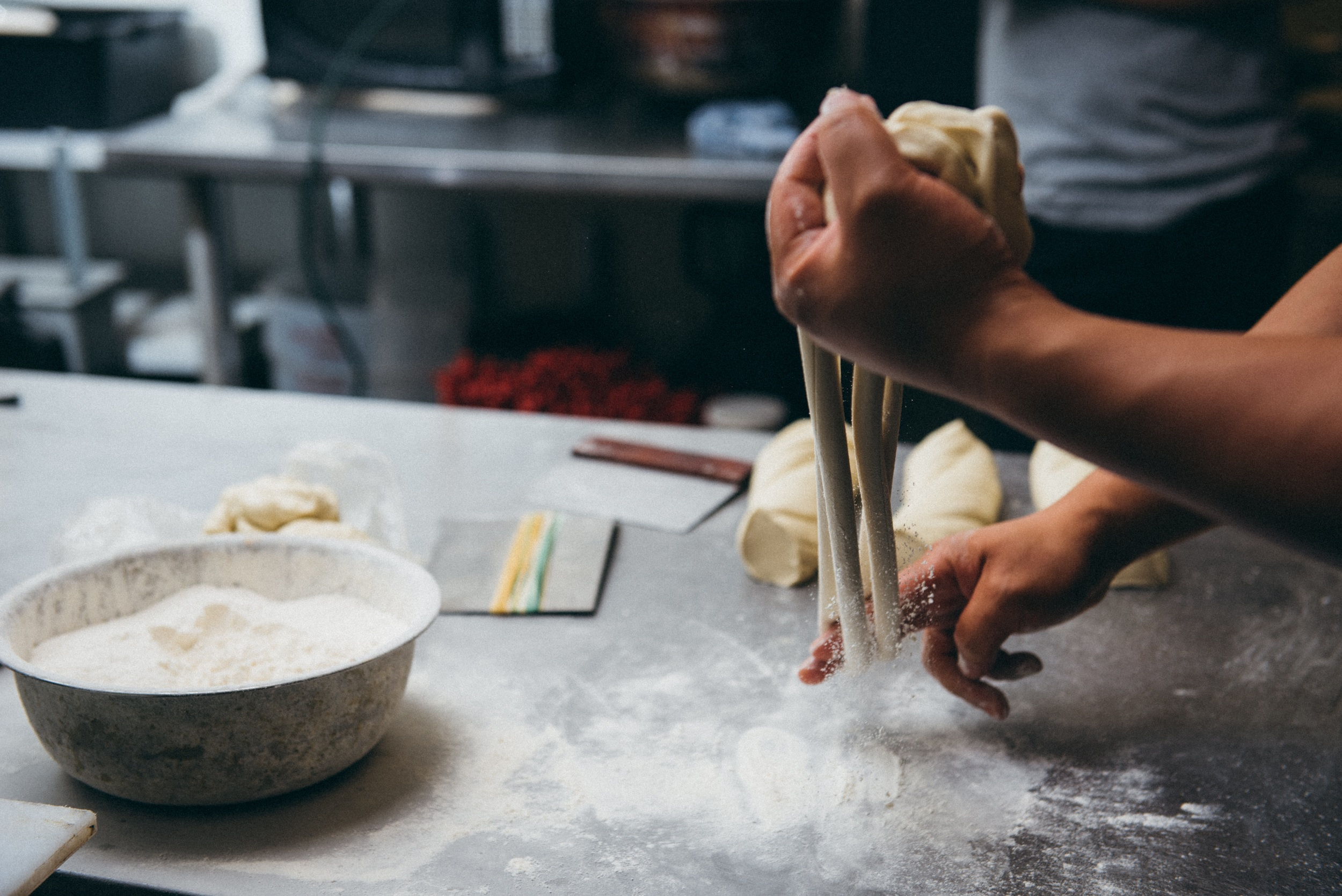 12. Jacob's strokes are precise and betray years of practice perfecting the art.  The speed of this process becomes evident, even in a photograph as the flour explodes off of the dough.