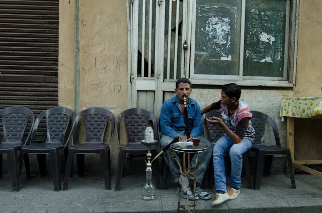man and son converse over hookah on cairo street.jpeg