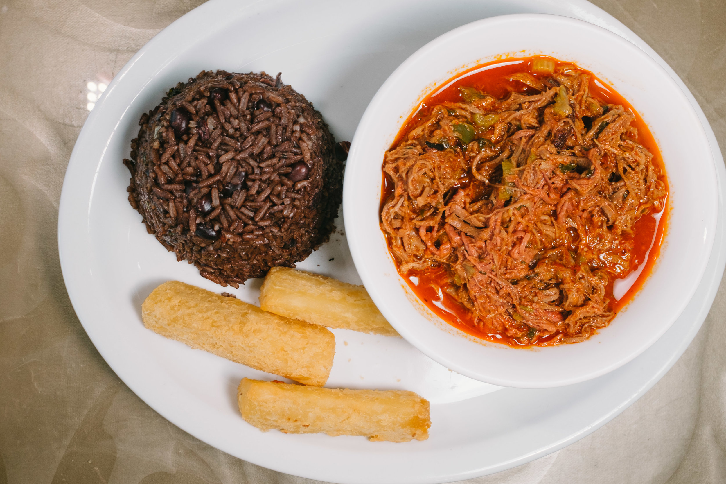 "Ropa Vieja is the national dish of Cuba.  Translated literally, it means ""old clothes,"" which this shredded beef dish resembles.  Typical sides include fried yucca and mixed rice and beans, and plantains."