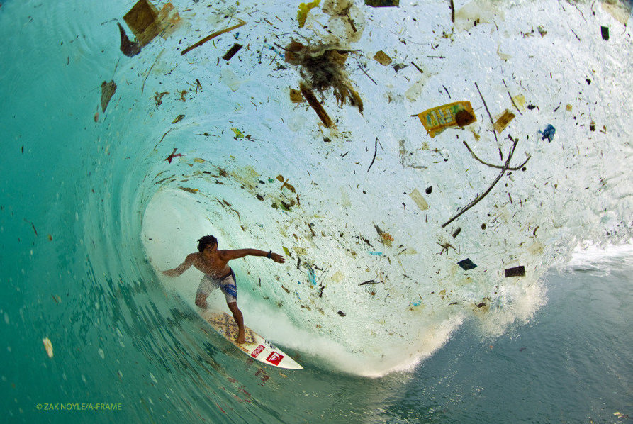 """""""In 2012,photographer Zak Noyle captured the Indonesian surfer Dede Surinaya surfing in waters choked with trash off the coast of Java, Indonesia."""" View more via  Huffington Post's article """"The Oceans Are Drowning In Plastic — And No One's Paying Attention"""""""