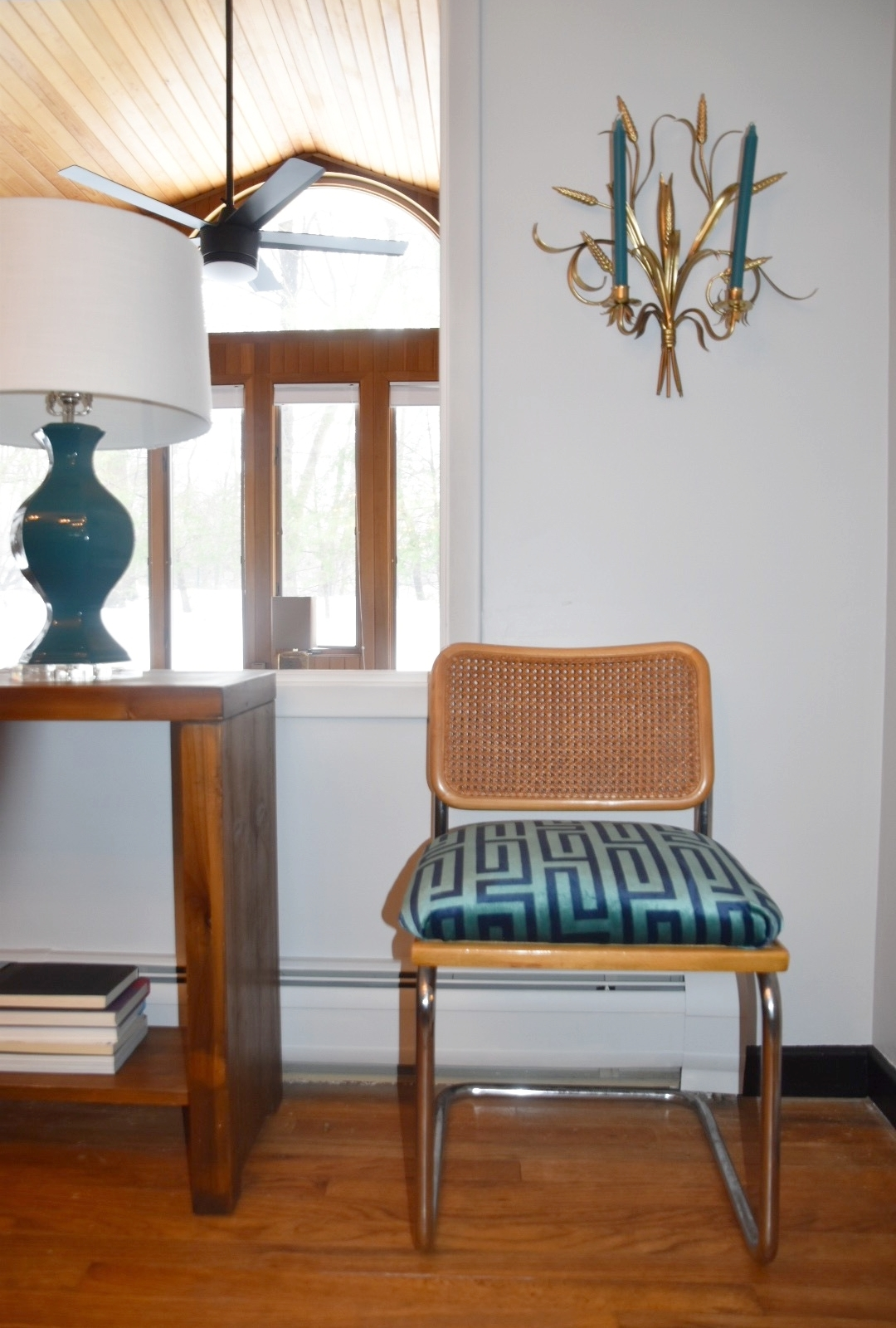 Cesca chairs and wheat sconce lend to a midcentury feel, while the Greek key fabric and Lucite base lamp add a modern lux layer to the space.