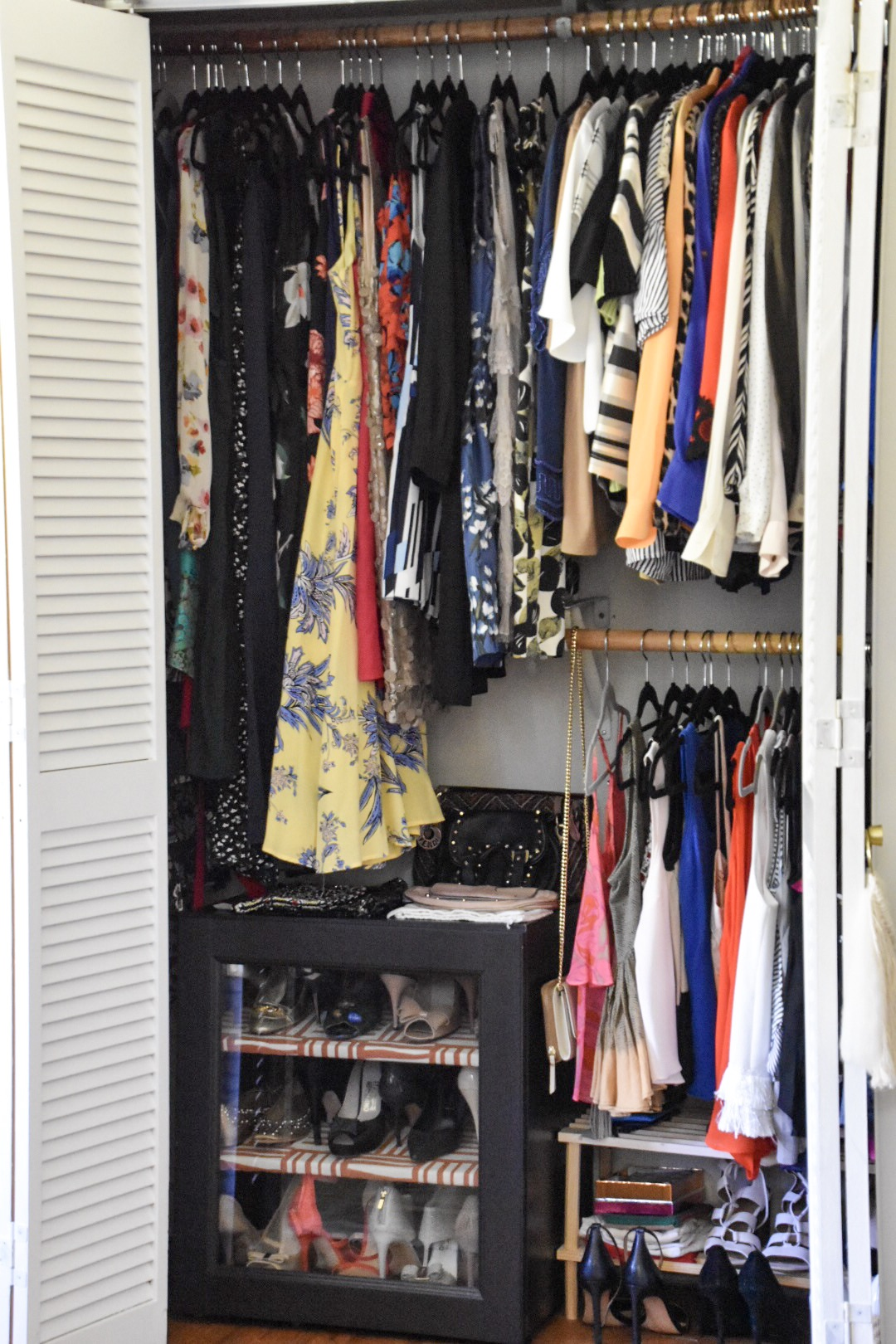 organized colorful closet with velevt hangers and shoe cabinet by the rath project