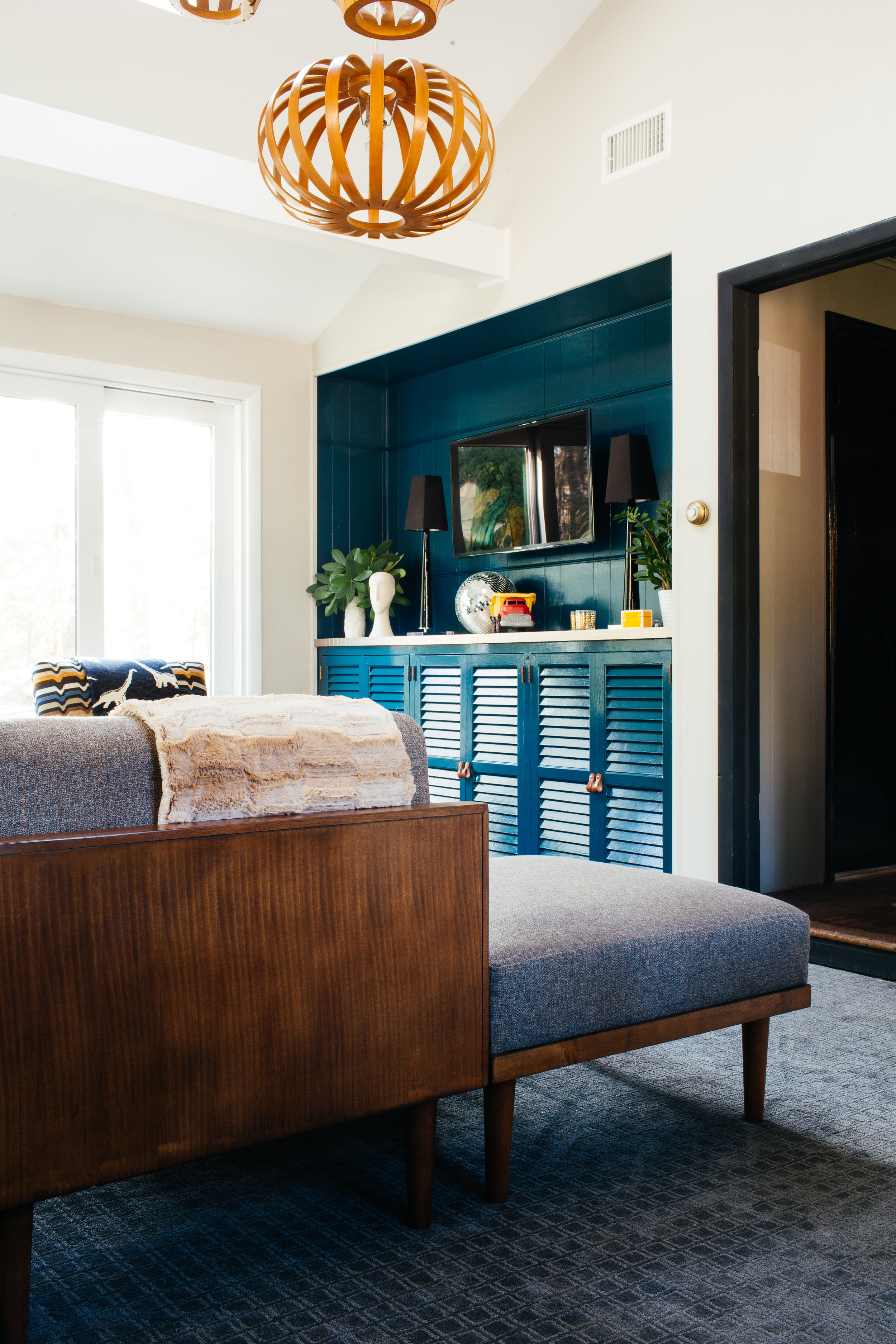 modern eclectic colorful family room design- deep teal built in cabinetry by the rath project