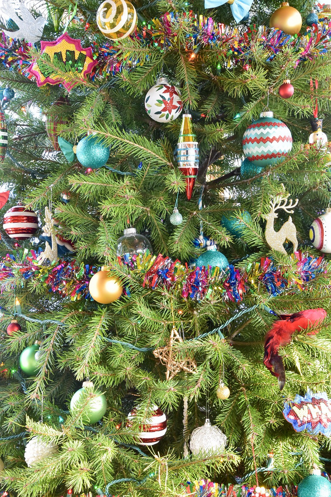 Colorful ornaments and rainbow tinsel fill a Christmas tree  by the rath project