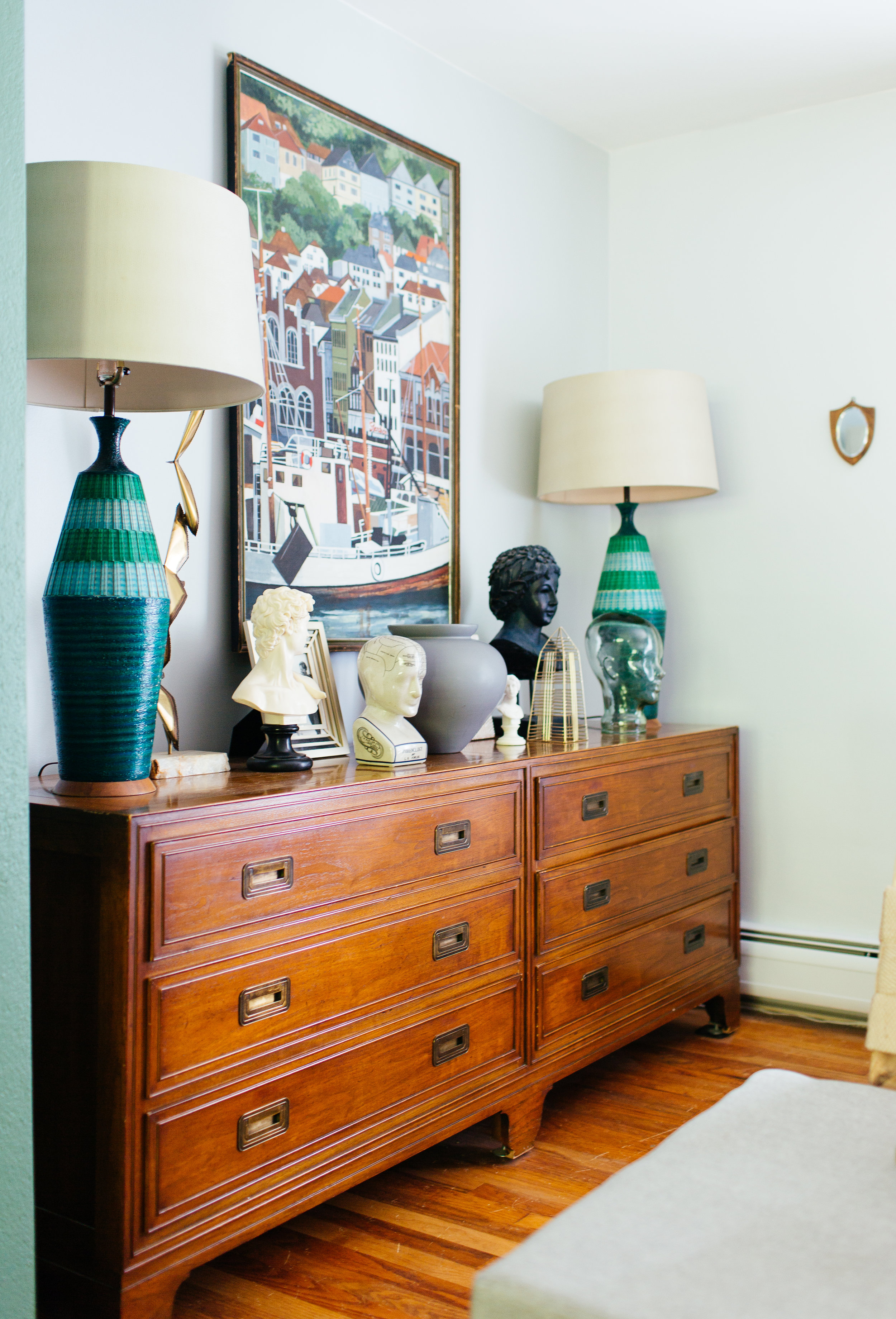 bust collection on mid century dresser in eclectic living room design by the rath project
