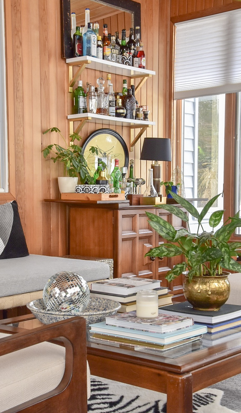 Mid century Modern Eclectic wood paneled Sunroom with styled bar by the rath project