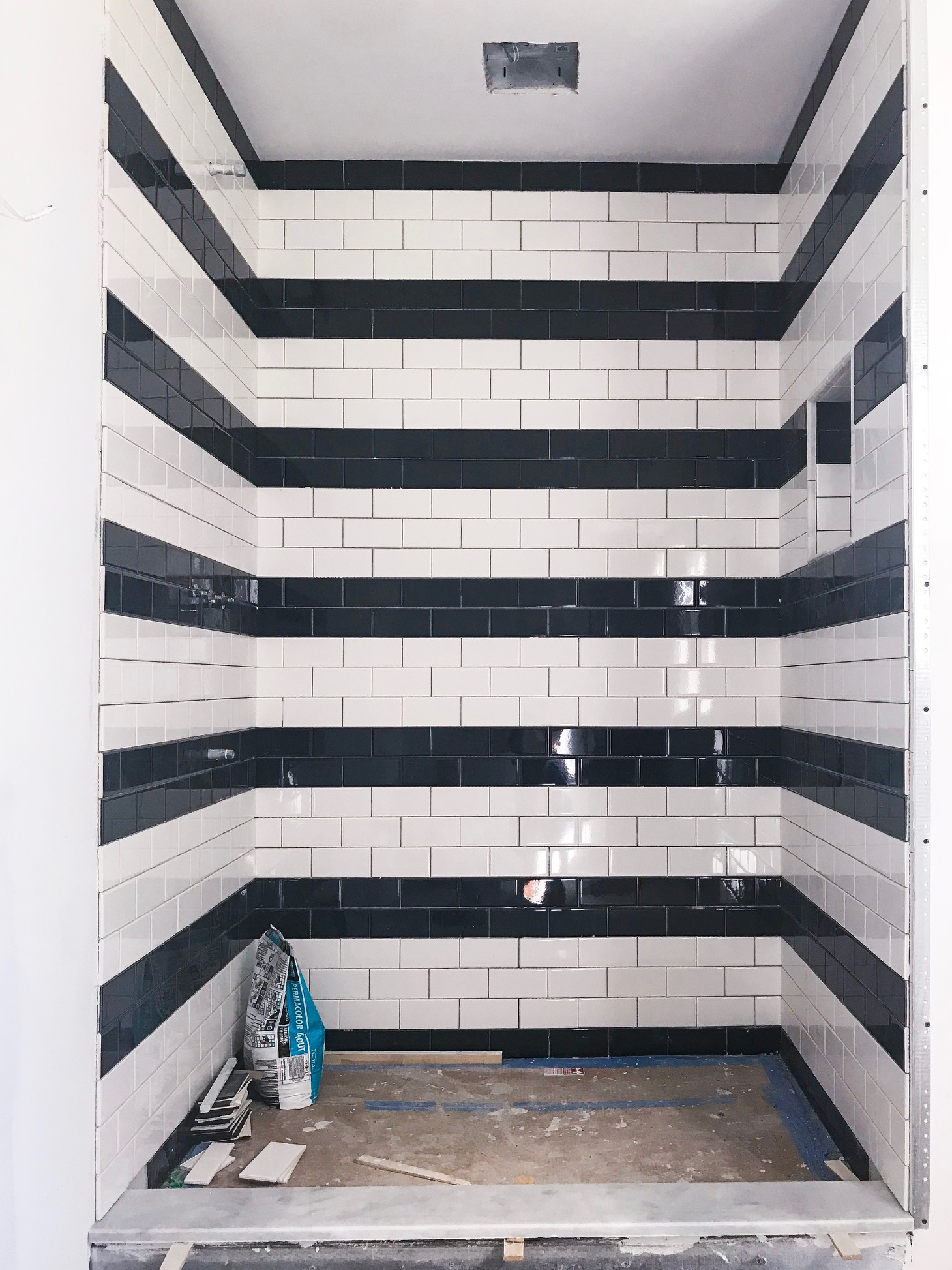 balck and white bands subway tile design in  shower by the rath project