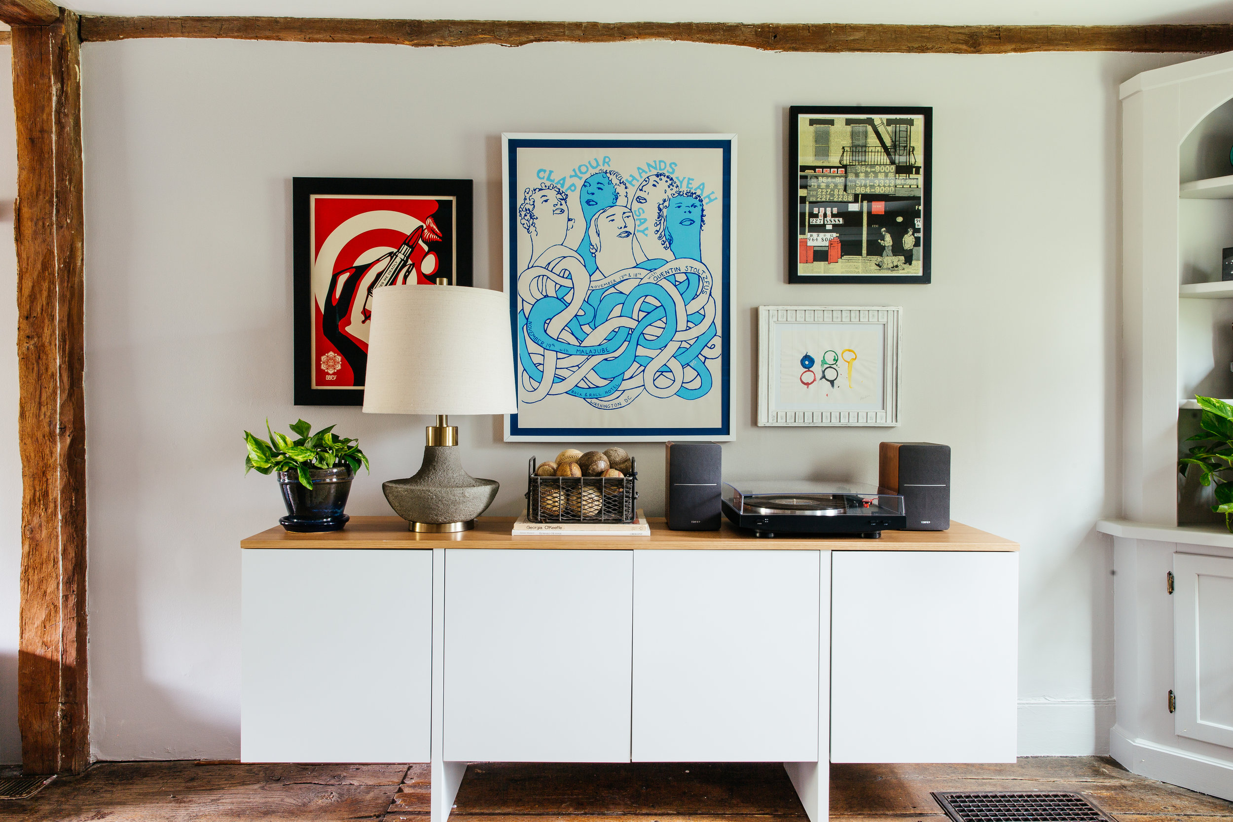 Antique farmhouse turned mid mod living room design with white console and collected gallery wall by the rath project