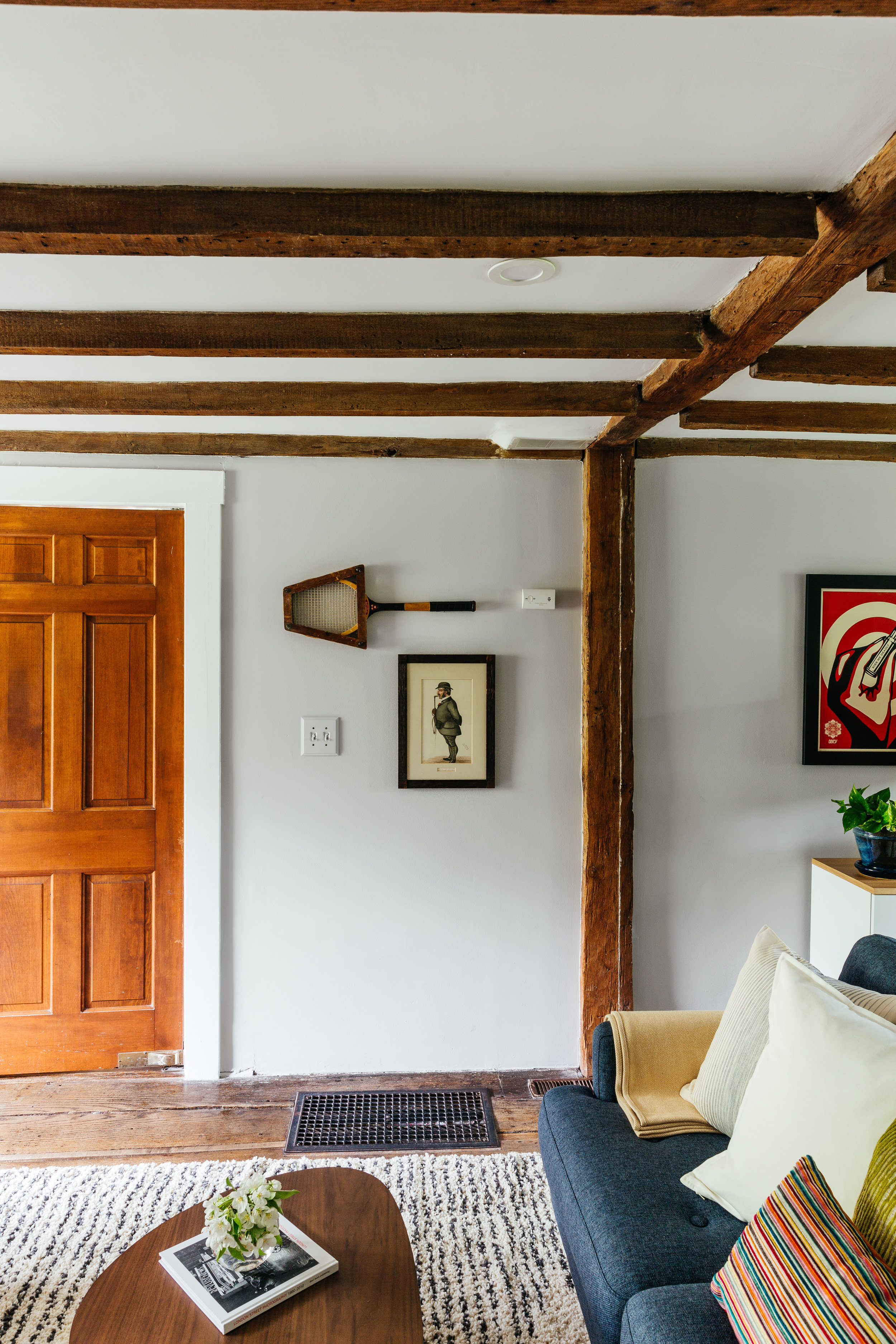 Antique farmhouse turned mid mod living room  with exposed beams design by the rath project