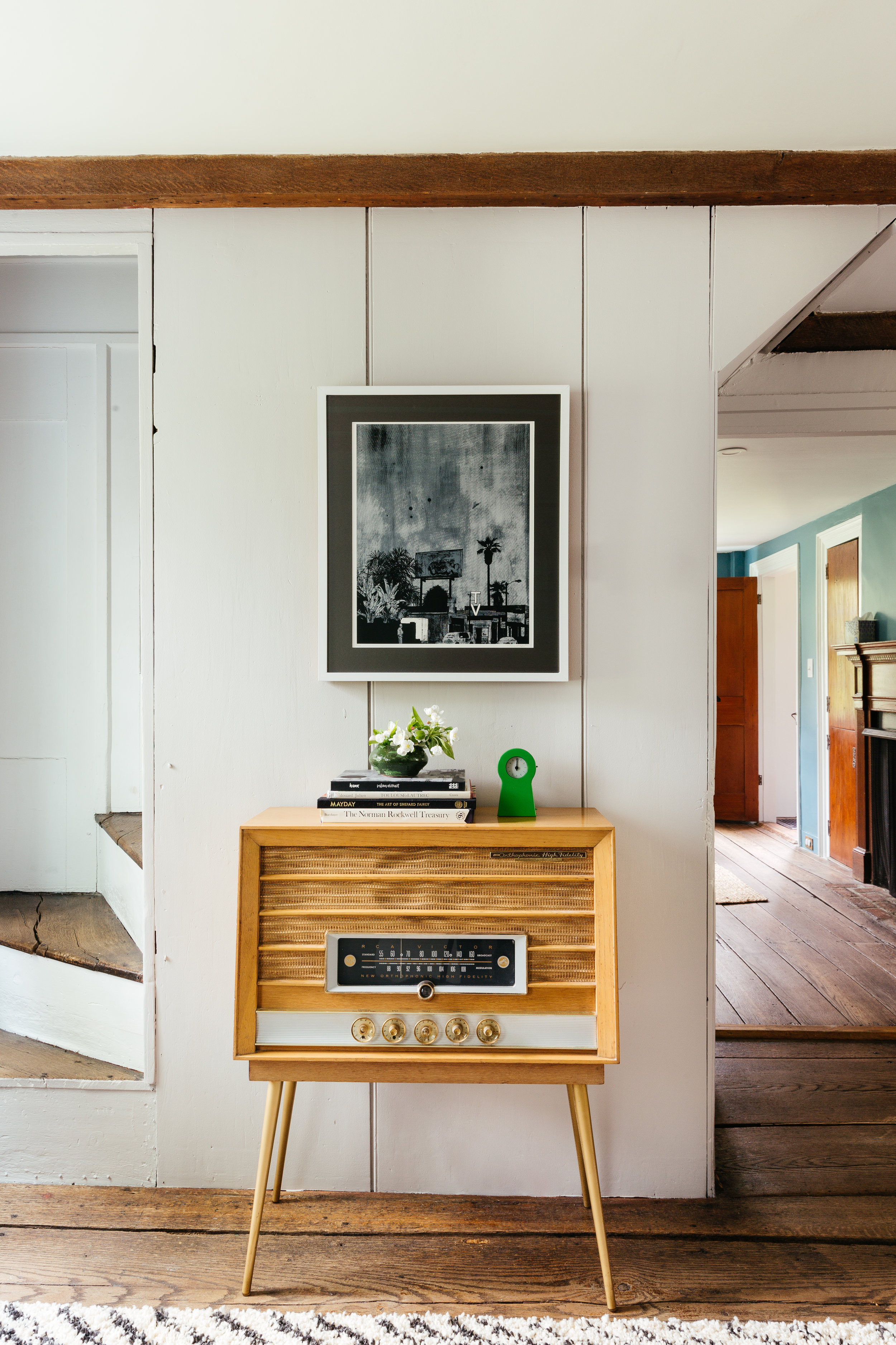 vintage radio in the listening area of a retro mid mod living room of an antique CT farmhouse  designed by The Rath Project