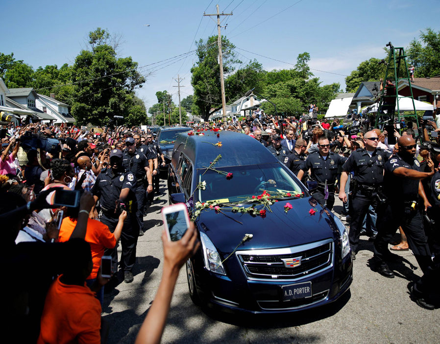 Masses swarm the hearse carrying Ali's coffin.