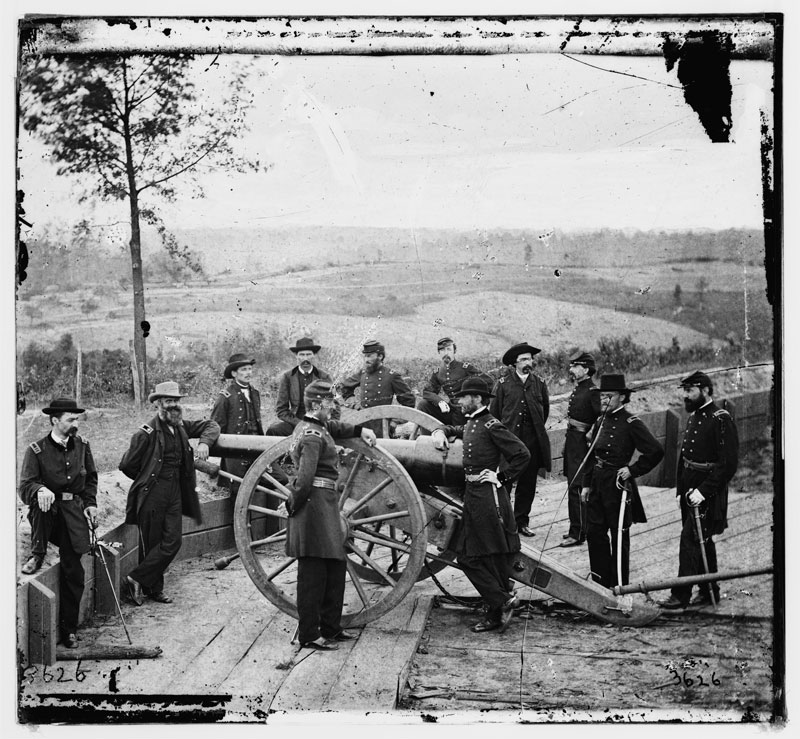 Gen. William T. Sherman, leaning on breach of gun, with staff at Federal Fort No. 7 in Atlanta, 1864. Courtesy of the Library of Congress.