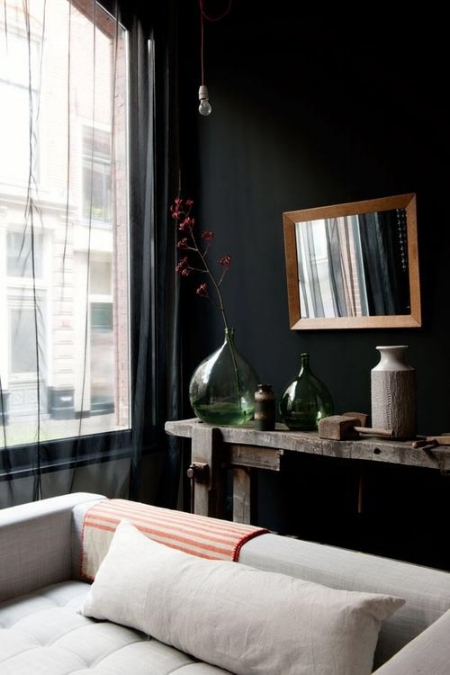 Black walls and black sheer drapes cast a backdrop to all things neutral in this cozy living area. Image via Mad about the House