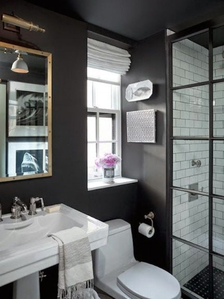 Black walls, shower door hardware, and shower floor tile make this bathroom a complete stunner. Image via Traditional Home