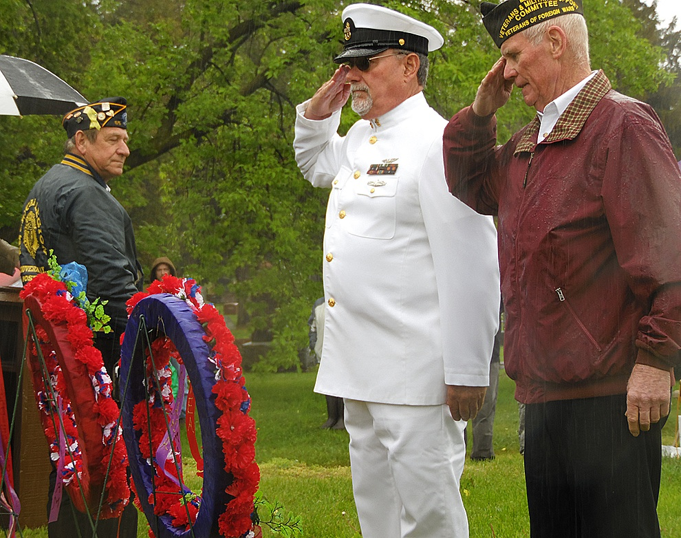 Michael Knowlton saluting after placing the ribbon to remember those who died in service in Panama. Joining in the salute is Mike Webster. (Rachel Hunter photo)