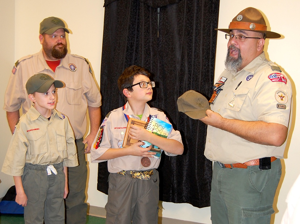Jack Velez receives Boy Scout Handbook and Scout Cap from Troop Scoutmaster Chris Velez while Assistant Scoutmaster Justin Bristol and Boy Scout Kyle Bristol look on. (photo provided)