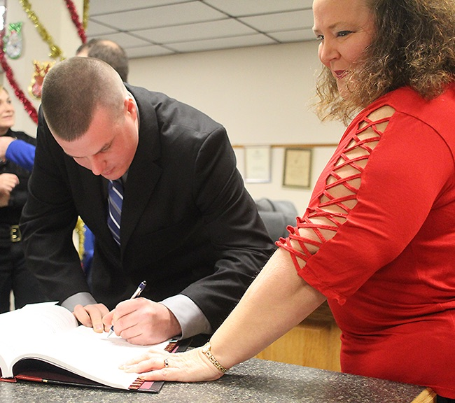 Nathan B. Sheen of Gouverneur (left) signing the oath of office as he was welcomed to the Gouverneur Police Department in an official ceremony on Wednesday, January 2. The oath was administrated by Village of Gouverneur Clerk and Treasurer Barbara Finnie (right). (Rachel Hunter photo)
