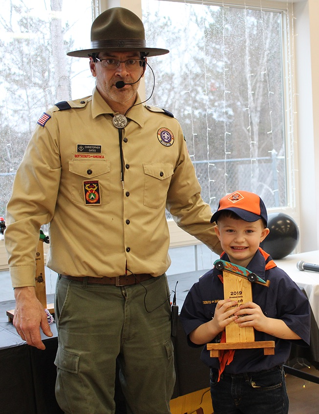 Abel Halladay won the Coolest Paint Job trophy for the bright flames that adorned his pinewood derby car. Abel Halladay is pictured (at right) with Cubmaster Chris Gates (at left). (Rachel Hunter photo)