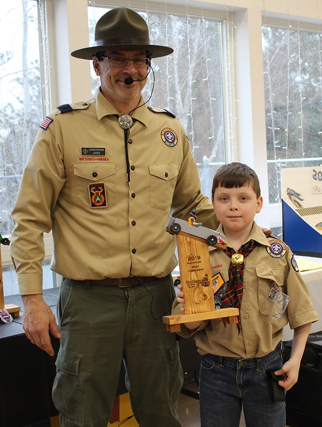 Mitchell Romans won the Most Outrageous trophy for his shark-themed pinewood derby car. Mitchell Romans is pictured (at right) with Cubmaster Chris Gates (at left). (Rachel Hunter photo)